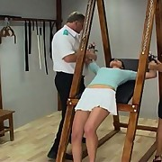 Upended to expose her bum to brutal punishment, she's vulnerable to their whims