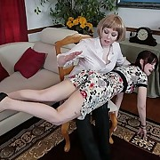 Blonde woman spanks a girl with a belt