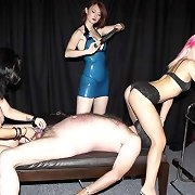 A threesome of dominatrixes works over a penitent captive