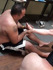 Two slaves did a feet massage to their tattooed mistress.