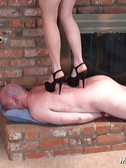 Merciless ebony walking with her sharp heel on the slave