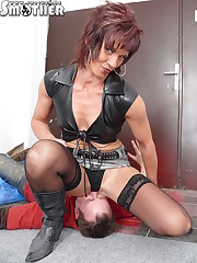 Dominatrix in skirt sat on slave