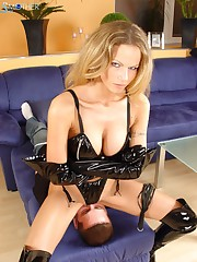 The mistress worn in black latex sits on a slaveman