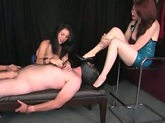 A trio of FemDoms teases and torments their bound male captive
