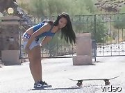 Cornine in panties riding a skateboard in the parking lot