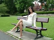 A baby walks in the park wearing cream heels