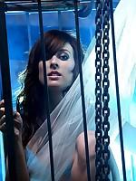 Brunette struggles in a square cage