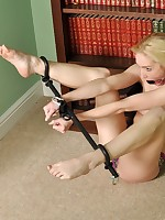 Blond virago encased in steel spreader bars