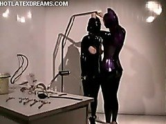 Submissive man hooded and tormented by dominatrix in latex catsuit.