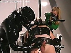 Submissive girl in latex suit with breast cut-outs in bondage.