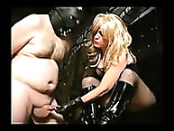 Latex  woman pulling slave cock and spanking