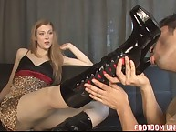 Dominatrix in leather high boots humiliates her slave