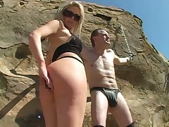 Tow-haired domme Shayne Ryder distressing a malesub locked on touching a stone.