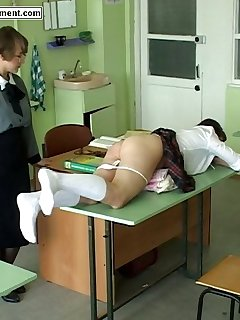 16 of Georgious girl is severely paddled over a desk in the classroom