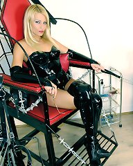 A Mistress pleasures herself while keeping her slave under control in a cramped birdcage