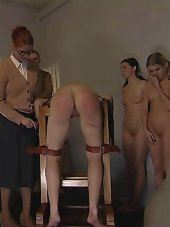 Tearful young girl tied over a bench for a brutal caning