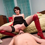 Beautiful mistress in high red boots on spike heels tramples her slave's cock before facesitting him