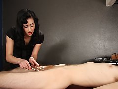 The sexy Mistress Nyxon grabs and twists his balls while digging her pointy bright red fingernails into his skin before tormenting him with an antique violet wand.