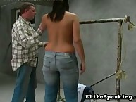 Bullwhipping for chubby topless brunette